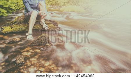 person sits on the stone covered with moss in the center of rapid flow of the river holding his feet in clear water against the background of juicy greenery