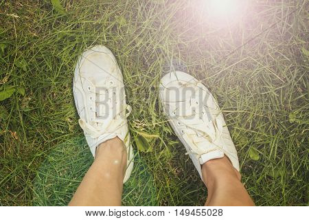 Woman in white shoes standing on a the beautiful green grass outdoors sunny summer day