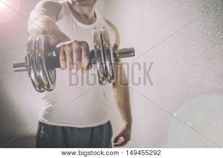man in a white shirt holding a metal dumbbell