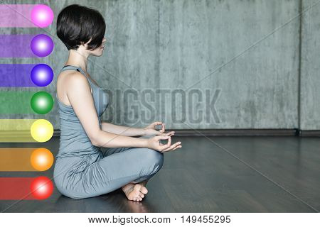 Woman practicing meditation with the chakras. Beautiful young woman doing yoga meditation in lotus posture with the activation of the chakras on the body