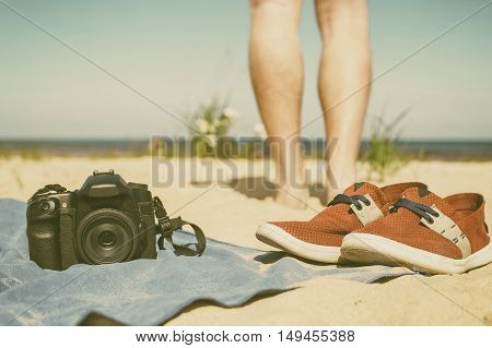 Camera with lens lying a towel on the sand at the beach standing beside red shoes and in the background can be seen the feet of the photographer looking at the sea