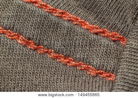 closeup macro red seam on a brown T-shirt fabric