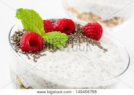 Chia yogurt with raspberries in a glass cup isolated on white background