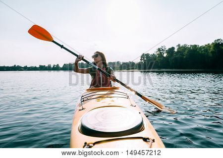 In search of adventures. Front view of beautiful young smiling woman kayaking on lake and smiling