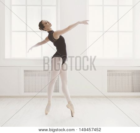 Classical Ballet dancer side view. Beautiful graceful ballerine in black practice ballet positions near large window in light hall. Ballet class training, high-key soft toning.