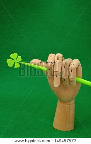 A mannequin hand holding a four leaf clover for St. Patrick's day