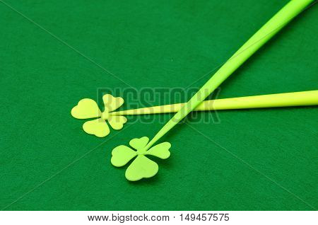 A four leaf clover on a stick isolated on a green background for St. Patrick's day