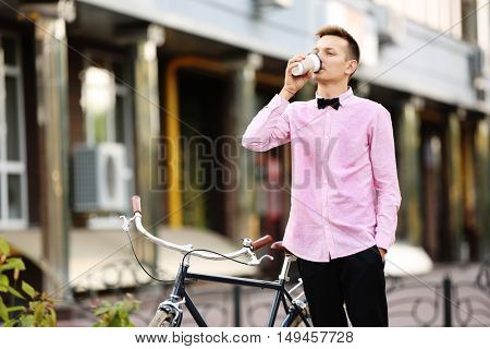 Young man in pink shirt with bicycle drinking coffee on street