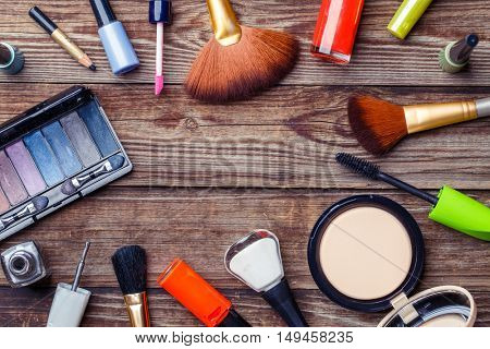 Make-up brushes and cosmetics on a wooden background