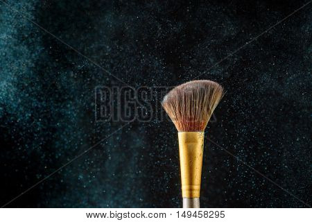 Item makeup - brush on black background with eye shadows