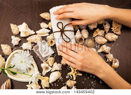Composition with hands, towel, flower and seashells