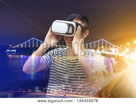 Double exposure. Young man wearing virtual reality glasses and city nightlife background. Modern technology concept.