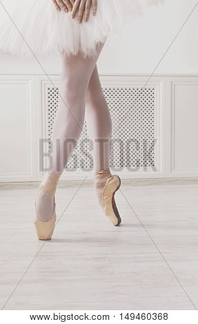 Closeup legs of young ballerina in pointe shoes at white class room background. Ballet practice on training. Beautiful slim graceful feet of ballet dancer in tutu skirt, unrecognizable female.