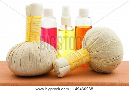 Concept of spa compress balls with bottles of aroma oil on wooden table