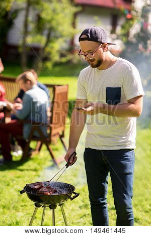 leisure, food, people, technology and holidays concept - man cooking meat on barbecue grill and texting message on smartphone at summer outdoor party