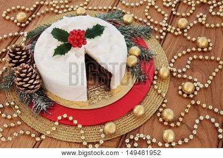 Traditional christmas cake with holly, snow covered winter greenery, gold bauble decorations with foil wrapped chocolate balls over oak background.