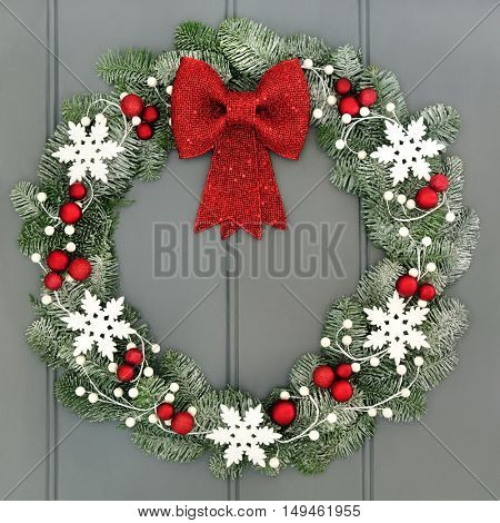 Christmas wreath with red baubles and bow and white snowflake decorations and snow covered blue spruce fir over grey front door background.