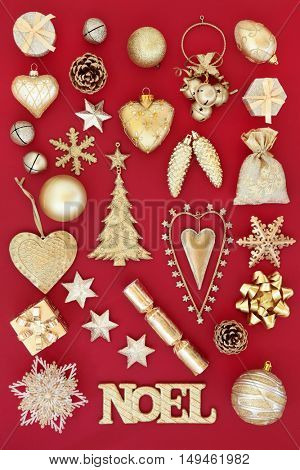 Gold noel sign and christmas tree decorations and baubles over red background.
