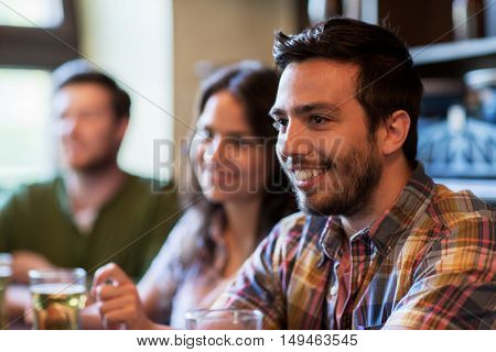 people, leisure, friendship and communication concept - happy man with friends drinking beer at bar or pub