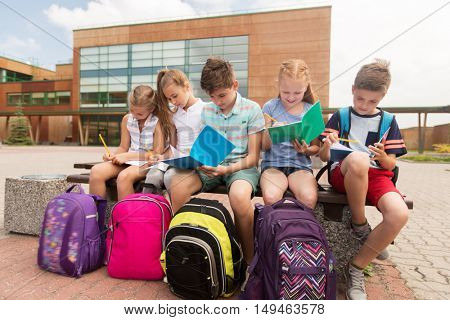 primary education, friendship, childhood, communication and people concept - group of happy elementary school students with backpacks and notebooks sitting on bench and doing homework outdoors