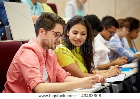 education, high school, university, learning and people concept - group of international students with notebooks writing at lecture