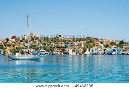 View over bay of Kastelorizo on sunny summer day. Island coast with typical colorful Greek houses, clear turquoise sea water and yacht. Dodecanese, Greece