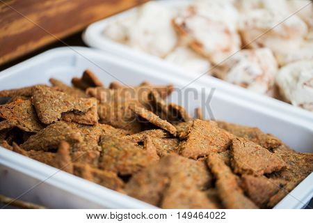 food, junk-food and sweets concept - close up of cookies or bread crisps on serving tray