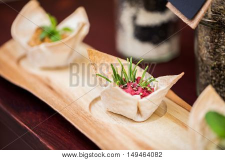 food, catering, cooking and eating concept - close up of dough cornet with beetroot filling