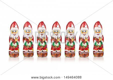 Closeup of Santa Claus chocolate figures in a row. Isolated on white background