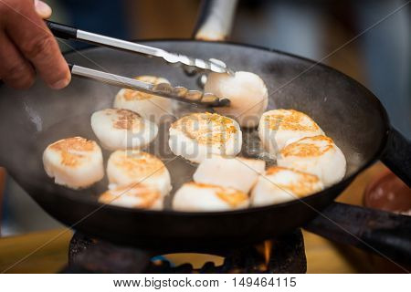 cooking, asian kitchen, sale and sea food concept - close up of cook with tongs frying scallops in cast iron pan at asian street market