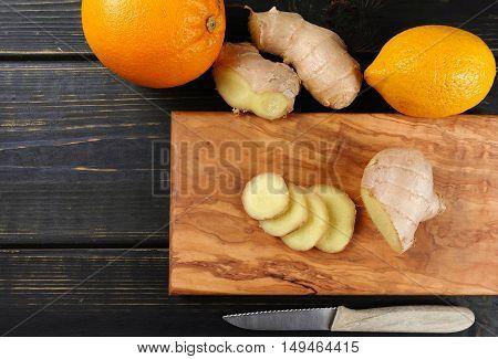 Natural flu and cold remedy - orange and lemon fruit fresh ginger over dark wooden background.