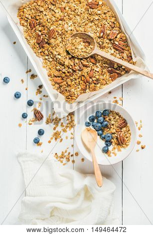 Healthy breakfast. Oat granola with pecan nuts, yogurt and blueberry in bowl on white wooden background, top view, vertical composition