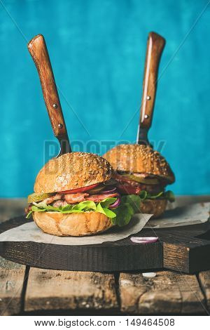 Homemade beef burgers with crispy bacon, onion rings, pickles, fresh vegetables and knives stuck in burgers on serving wooden board over rustic table, blue plywood wall at background, selective focus