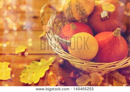 harvest, season, advertisement and autumn concept - close up of pumpkins in wicker basket with leaves on wooden table at home