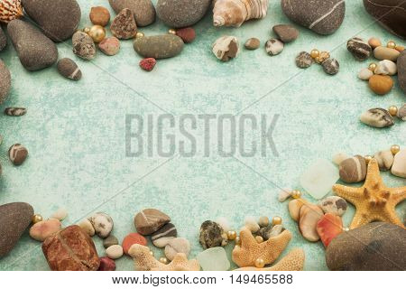 Abstract frame with stones, seashells and decorative pearl on blue background