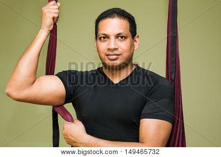 Man making aerial yoga exercises indoor aerial yoga
