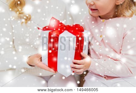 holidays, birthday, christmas, children and family concept - close up of mother and little girl with gift box at home