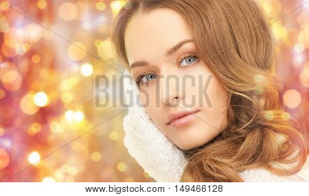 winter, holidays, christmas and people concept - close up of happy young woman in mittens touching her face over lights background