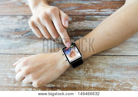 business, modern technology, communication and people concept - close up of female hands setting smart watch with incoming call on screen on wooden table