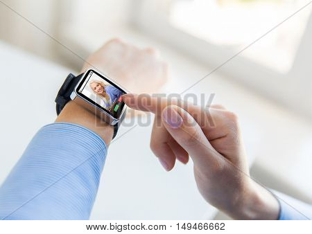business, modern technology, communication and people concept - close up of female hands setting smart watch with incoming call on screen at office