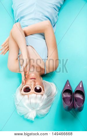 Top view of pretty young woman in blonde wig and sunglasses lying over blue background