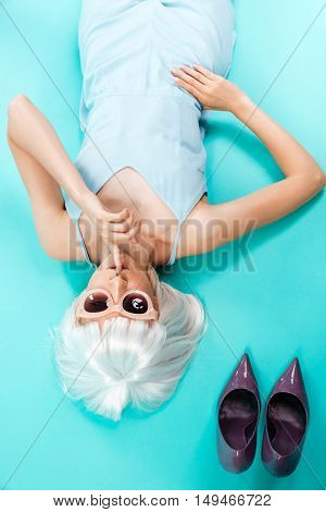 Top view of attractive young woman lying and showing silence sign over blue background