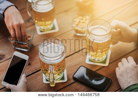people, leisure, friendship and technology concept - close up of friends with smartphones and snacks drinking beer at bar or pub