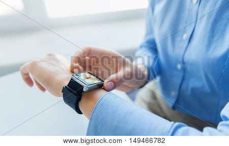 business, technology, navigation and people concept - close up of woman hands with gps navigator map on smart watch screen at office
