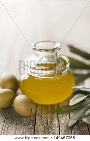 Olive oil in a bottle on a wooden table