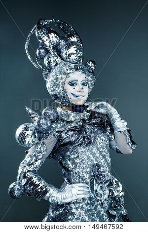 Portrait of young woman with creative silver make-up for carnival
