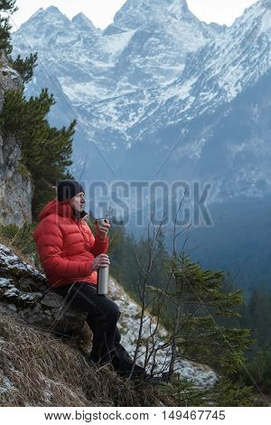 Man in winter mountains is resting and drinking from vacuum flask metal cup