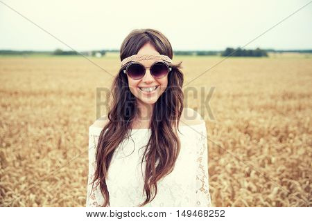 nature, summer, youth culture and people concept - smiling young hippie woman in sunglasses on cereal field