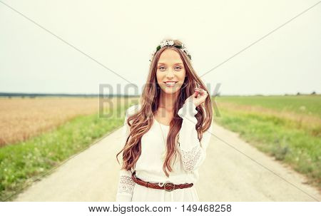 nature, summer, youth culture and people concept - smiling young hippie woman wearing flower wreath on cereal field