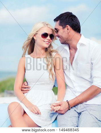 summer holidays and dating concept - couple in shades at seaside